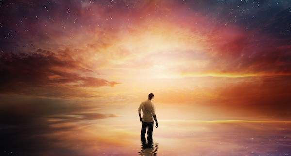A man looks up at a beautiful sunset with shining stars.